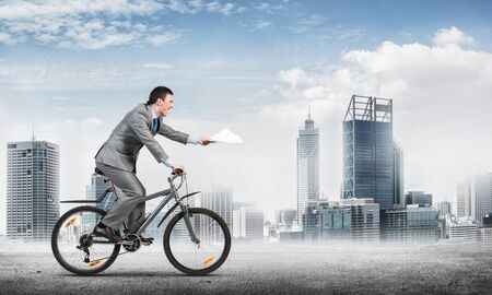 Businessman with paper documents in hand on bike. Courier with documents. Corporate employee in grey business suit riding bicycle on background of modern cityscape. Accounting and financial statements