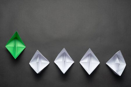 Flat lay green origami origami leader boat ahead others boats. Row of paper ships on black background. Individual motivation and direction. Creative innovation and leadership. Social marketing layout.