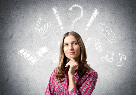 Brown haired woman thinking something project. Idea generation process. Creative media doodles on grey wall. Puzzled girl has serious facial expression. Woman wears red checkered shirt. Stok Fotoğraf