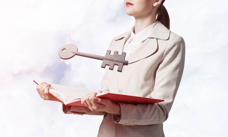 Woman showing big metal key above opened book. Real estate agency advertising. Sale and rent commercial and private real property. Elegant consultant with notebook on background of skyscape.