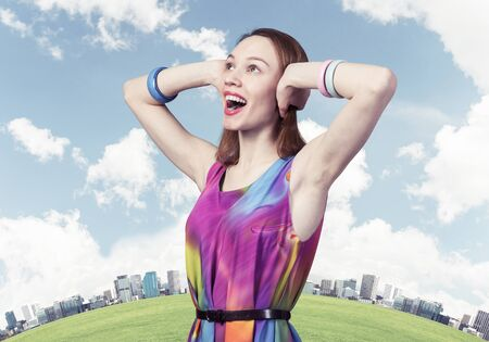 Redhead beautiful girl closing her ears with hands. Charming lady in bright colorful dress and bracelets on background modern cityscape. Portrait of happy young woman looking up aside with open mouth