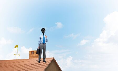 Faceless businessman with camera zoom instead of head standing on house roof Foto de archivo - 130801334
