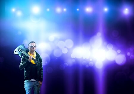 Young man rock musician in lights of stage