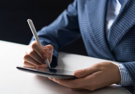 Man in business suit sitting at desk and working at tablet computer. Close-up of human hands holding pen and tablet gadget. Manager at workplace in office. Business and digital technology concept Imagens