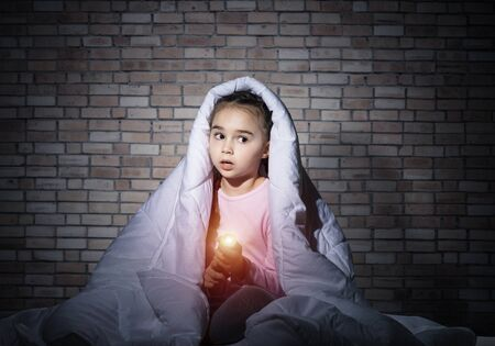 Frightened girl with flashlight hiding under blanket. Scared kid lying in his bed at home. Night terrors of child. Little girl afraid of dark. Child in pajamas on background of grey wall. Zdjęcie Seryjne
