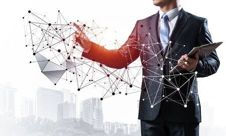 Businessman with documents pointing on abstract network with polygonal shapes. Standing entrepreneur in business suit and tie without face. Professional business assistance and consulting service.