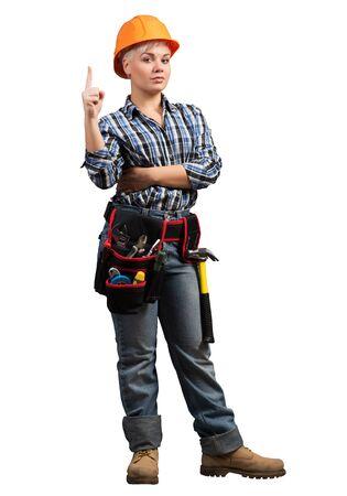 Schöner weiblicher professioneller Baumeister im Bauarbeiterhelm mit dem Finger, der nach oben zeigt. Porträt der jungen Frau im karierten blauen Hemd lokalisiert auf weißem Hintergrund. Industriearchitektur und Konstruktion