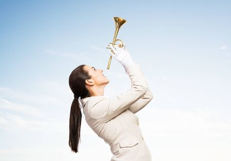 Beautiful woman playing trumpet brass. Young businesslady in white business suit and gloves posing with music instrument on blue sky background. Musician practicing and performing.