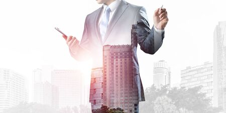 Businessman pointing on empty space on background modern cityscape. Standing entrepreneur in business suit and tie without face. Double exposure template. Blank screen ready for business message Banque d'images - 130740932