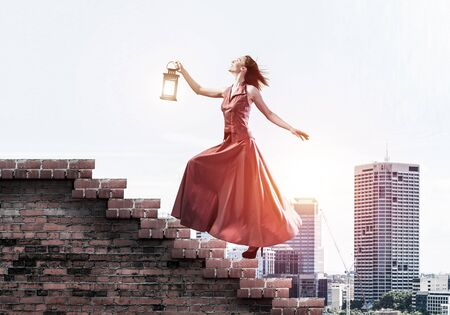Young attractive woman in red dress with lantern walking up staircase. Mixed media