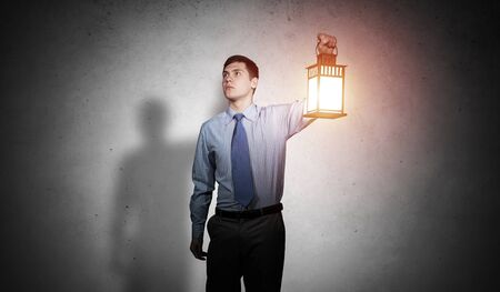 Businessman with glowing lantern looks suspicious on background grunge wall. Young corporate employee in shirt and tie looking for something at night. Portrait of distrustful man lost in dark.