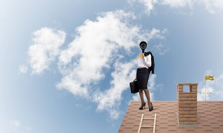 Faceless businesswoman with camera zoom instead of head standing on house roof Foto de archivo - 130741149