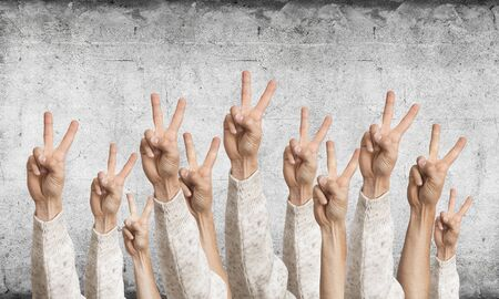 Row of man hands showing victory gesture. Winning or triumph group of signs. Human hands gesturing on background of grey wall. Many arms raised together and present popular gesture.