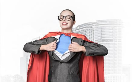 Portrait of business woman super heroine tearing off her shirt. Smiling business lady with closed eyes in red hero cape on blue sky and cityscape background. Brave super woman dreaming about new wins