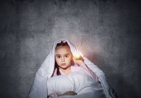 Frightened girl with flashlight hiding under blanket. Scared kid lying in his bed at home. Night terrors of child. Little girl afraid of dark. Child in pajamas on background of grey wall. Фото со стока