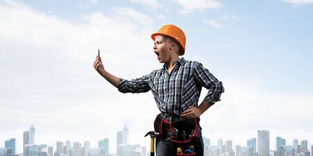 Expressive blonde woman in workwear and hardhat shouting into smartphone. Portrait of young emotional worker in checkered blue shirt standing with open mouth. Business communication and conversation. Banco de Imagens