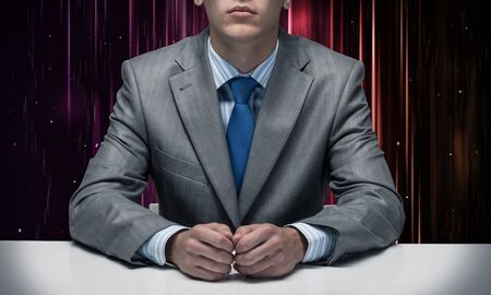Man with folded hands sitting at desk. Internet manager without face in business suit and tie on abstract matrix like background. Digital technologies and innovations. Internet company service