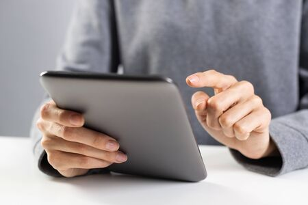 Close-up of female hands touching screen of digital tablet. Businesswoman sitting at desk and working at tablet computer. Consultant at workplace in office. Business and digital technology concept.