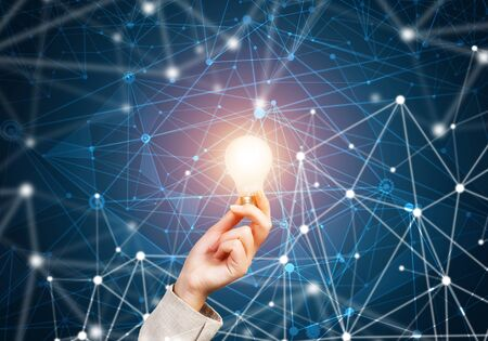 Woman hand holding glowing light bulb and abstract network structure on background of dark wall. Science research and innovative solution. Global cloud technology and internet communication concept