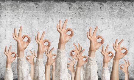 Row of man hands in white sweater showing okay gesture. Agreement and approval group of signs. Human hands gesturing on background of grey wall. Many arms raised together and present popular gesture. Banco de Imagens