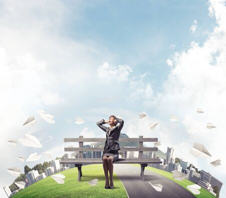 Stressful woman sitting on wooden bench. Emotional screaming girl keeps hands on head. Businesswoman in despair. City panorama with round horizon of world and flying paper planes. Woman call for help. Stok Fotoğraf