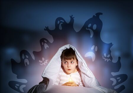 Surprised boy with flashlight hiding under blanket. Amazed kid sitting in his bed at home. Fear of the dark. Little child in pajamas afraid of ghosts at night. Nightmare fantasy and imagination.