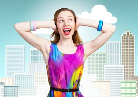 Redhead beautiful girl closing her ears with hands. Charming lady in bright colorful dress and bracelets on background cartoon cityscape. Portrait of happy young woman looking up aside with open mouth