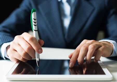 Man in business suit using tablet computer. Close-up of male hands holding pen and tablet gadget. Businessman at workplace in office. Mobile smart device in business occupation. Digital technology Imagens
