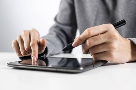 Woman using digital tablet computer at office desk. Close-up of female hand holding pen and touching screen of tablet device. Business woman at workplace. Mobile smart device in business occupation.