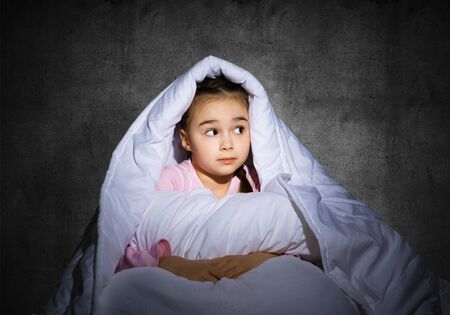 Frightened girl hiding under blanket. Scared kid lying in his bed at home. Fear of the dark. Beautiful little girl can not sleep at night. Portrait of child in pajamas on background of grey wall. Фото со стока
