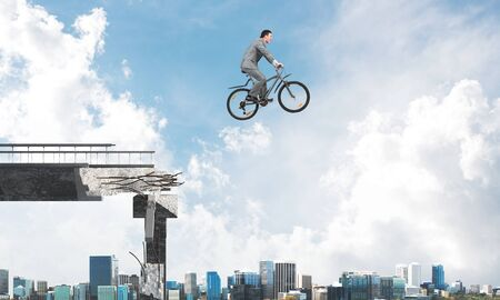 Businessman on bike jumping from broken bridge. Man wearing business suit riding bicycle in air. Cyclist on background of cityscape and blue sky. Business person having fun on bicycle outdoor.