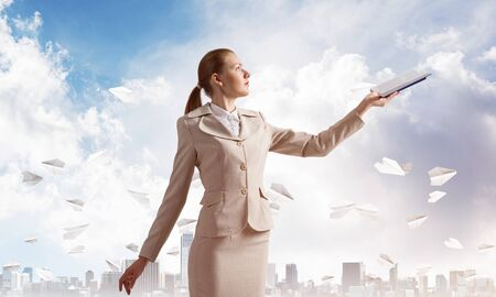 Attractive woman holding open notebook on background of cityscape and paper planes in blue sky. Elegant young woman in white business suit with open book in hands. Internship and practice in company.