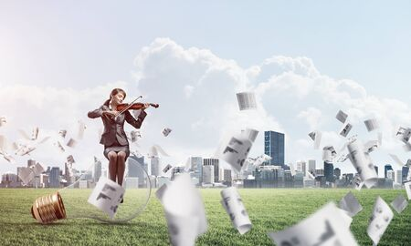 Young woman with violin sitting on glowing lamp. Businesslady playing violin on green meadow with falling paper documents. Musician practicing and performing. Business infographics and analytics. Banque d'images
