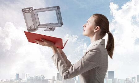 Woman holding open notebook with flying computer 3d model. Engineering and construction of computer system. Elegant lady on background of modern cityscape and sky. Hi-tech concept with virtual reality