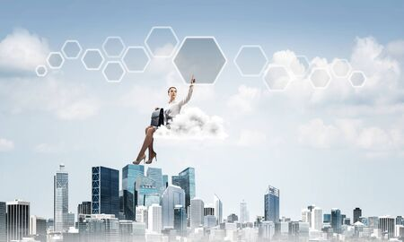 Businesswoman sit on cloud over city and pointing at icon in air Stok Fotoğraf