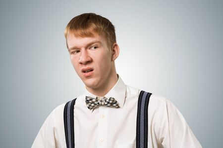 Distrustful redhead hipster looking at camera with suspicion and uncertainty. Skeptical boy has dissatisfied facial expression. Portrait of guy wears shirt, bow tie and suspenders on grey background Stockfoto