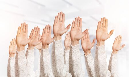 Row of man hands showing voting gesture. Participation and agreement group of signs. Human hands gesturing on light blurred background. Many arms raised together and present popular gesture.