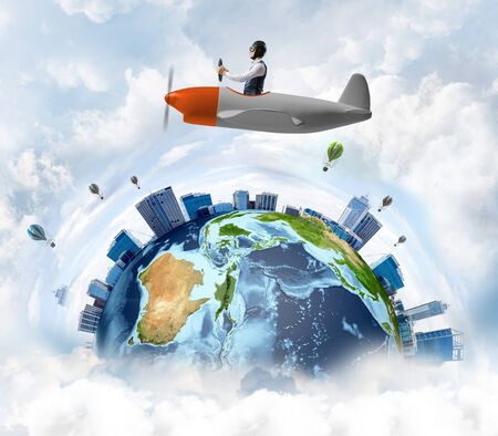 Young man in aviator hat with goggles driving propeller plane. Traveling around the world by airplane concept. Funny man flying in small airplane in sky with clouds. Round earth with skyscrapers.
