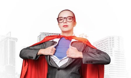 Beautiful business woman opening her shirt like a superhero. Confident lady in glasses with red hero cape. Brave super woman ready for new wins. Woman wears superhero t-shirt under her business suit.