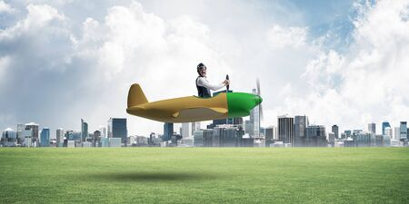 Young aviator driving small propeller plane. Modern metropolis with high buildings on background. Man in airplane flying low above ground. Dreaming and imagination mixed media concept.