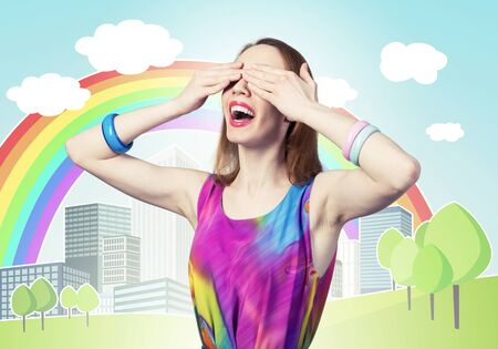 Redhead beautiful woman with hands covering eyes. Elegant lady in bright dress and bracelets. Flirty girl posing on background cartoon city with rainbow. Young woman waiting for pleasant surprise. 스톡 콘텐츠 - 130931314