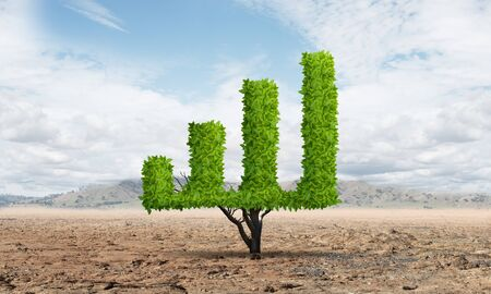 Green plant in shape of growth financial graph in desert. Business analytics and statistics. Friendly ecosystem for business and investment. Nature landscape with dry soil and blue sky.
