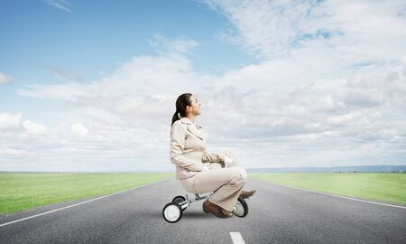 Beautiful young woman riding childrens bicycle on asphalt road. Businesslady in white business suit cycling small bike outdoor. Nature landscape with green grass. Professional career start concept