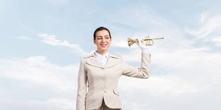 Beautiful woman holding trumpet brass near ear and listening. Young business lady in white business suit and gloves posing with music instrument on blue sky background.