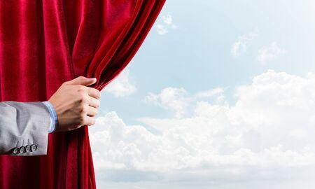 La mano humana abre la cortina de terciopelo rojo sobre fondo de cielo azul Foto de archivo