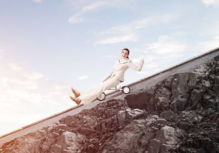 Beautiful happy woman riding downhill on mountain road. Young employee in white business suit going down on small bike outdoor. Professional career start. Beginner level business concept.