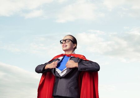 Portrait of business woman super heroine tearing off her shirt. Smiling business lady with closed eyes in red hero cape on blue sky background. Brave super woman dreaming about new wins Foto de archivo