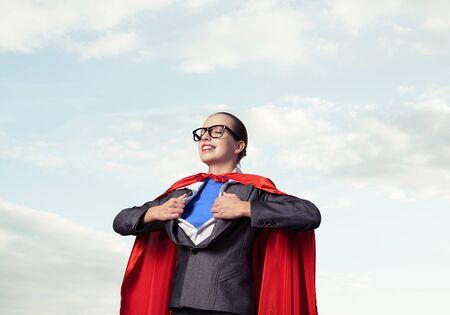 Retrato de mujer de negocios super heroína arrancándose la camisa. Señora de negocios sonriente con los ojos cerrados en capa de héroe rojo sobre fondo de cielo azul. Valiente super mujer soñando con nuevas victorias Foto de archivo