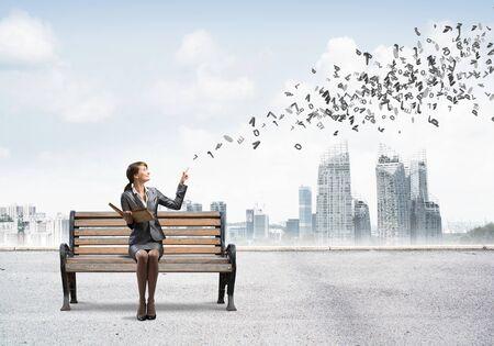 Mujer joven sosteniendo un libro abierto y sentado en un banco de madera. Hermosa chica en traje de negocios mirando hacia arriba y apuntando a varias cartas volando en aire. Educación de negocios. Asistencia y consultoría