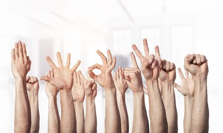 Row of man hands showing various gestures. Ok, finger pointing, victory, spread fingers, clenched fist and thumb up signs. Human hands gesturing on light blurred background. Many arms raised together.